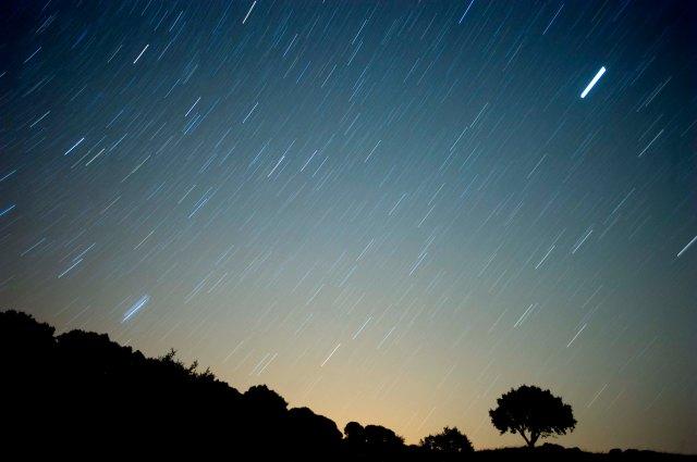 A meteor streaks across the sky against